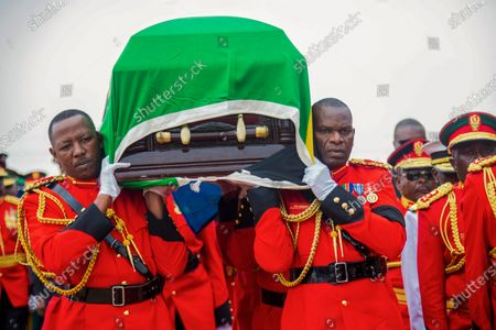 Military officers carry the coffin of former President John Magufuli, draped with the national flag, during a funeral service in his home town of Chato, Tanzania, . Some thousands have gathered in the northwestern town of Chato for the burial of former Tanzanian President John Magufuli whose denial of COVID-19 brought the country international criticism