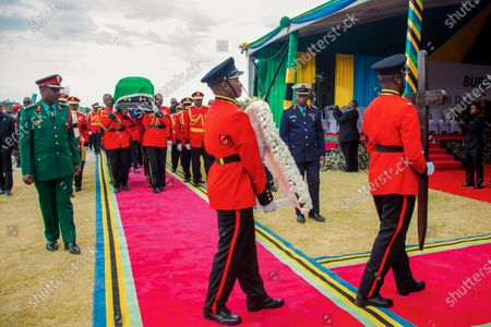 Military officers carry the coffin of former President John Magufuli, draped with the national flag, during a funeral service in his home town of Chato, Tanzania . Thousands have gathered in the northwestern town of Chato for the burial of former Tanzanian President John Magufuli whose denial of COVID-19 brought the country international criticism