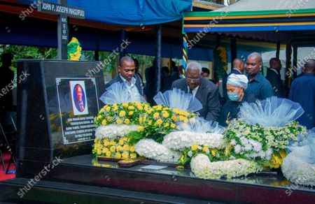 Stock Photo of Mourners place flowers on the grave of former President John Magufuli in his home town of Chato, Tanzania . Thousands have gathered in the northwestern town of Chato for the burial of former Tanzanian President John Magufuli whose denial of COVID-19 brought the country international criticism