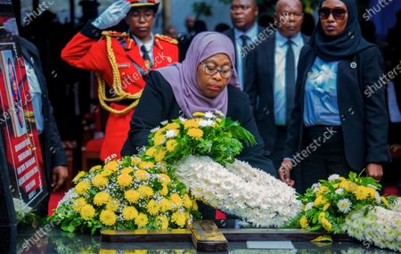 President Samia Suluhu Hassan places flowers on the grave of former President John Magufuli in his home town of Chato, Tanzania . Thousands have gathered in the northwestern town of Chato for the burial of former Tanzanian President John Magufuli whose denial of COVID-19 brought the country international criticism