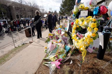 Wreaths and other tributes envelope a police cruiser as Boulder County, Colo., District Attorney Michael Dougherty, at the podium, makes a point to outline the ongoing investigation into the mass shooting at a King Soopers grocery store during a news conference outside police headquarters, in Boulder, Colo. Ten people were killed in the shooting at the supermarket on Monday