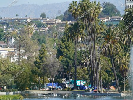 Los Angeles City Sanitation trucks are seen under palm trees around tents set on the north side of Echo Park Lake in Los Angeles . A newly installed fence surrounded the park Thursday after a late-night confrontation between police and vocal demonstrators who oppose the city's effort to remove a large homeless encampment and perform extensive repairs of the site. The encampment has been the site of drug overdoses, assaults, and shootings, with four deaths in the park over the past year, according to a statement from City Councilmember Mitch O'Farrell's office