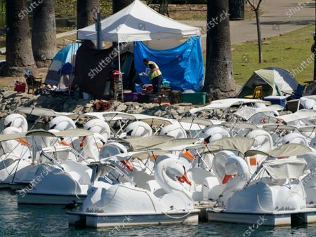 Los Angeles City LASAN CARE, Cleaning, and Rapid Engagement team member documents the tents on the east side of Echo Park Lake before their removal in Los Angeles . The encampment has been the site of drug overdoses, assaults, and shootings, with four deaths in the park over the past year, according to a statement from City Councilmember Mitch O'Farrell's office