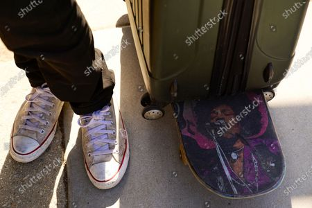 """Echo Park homeless encampment resident Robert """"Bobby"""" Rodriguez wheels an empty suitcase on a Jimi Hendrix themed skateboard outside the perimeter of Echo Park Lake trying to recover his belongings, in Los Angels. Rodriguez was unable to return to his tent when the fence went up and was worried about his belongings would be taken to another location. Authorities moved in late Thursday in to evict residents of the large homeless encampment despite protests by the people who live there and their supporters"""