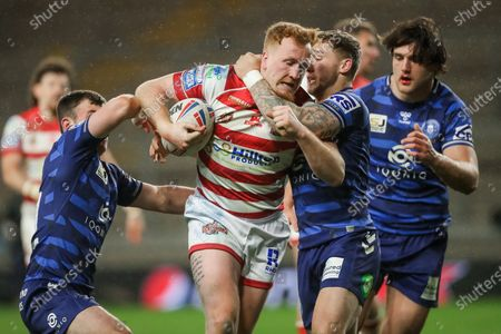 Leigh's Jordan Thompson is tackled by Wigan's Sam Powell and Harry Smith.