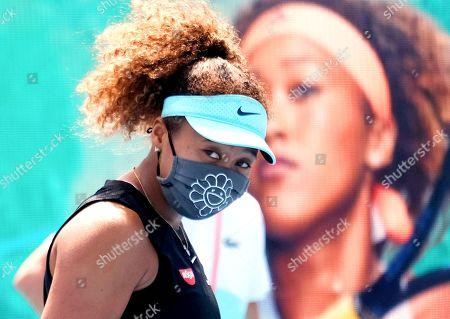 Naomi Osaka from Japan puts on a mask and celebrates after defeating Ajla Tomljanovic from Australia