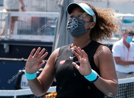 Naomi Osaka from Japan puts on a mask and waves to friends in the stands after defeating Ajla Tomljanovic from Australia