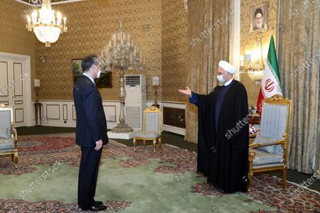In this photo released by the official website of the office of the Iranian Presidency, President Hassan Rouhani, right, welcomes Chinese Foreign Minister Wang Yi at the start of their meeting, in Tehran, Iran