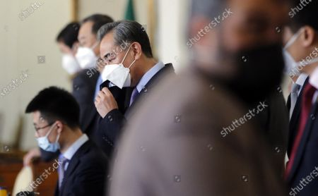 Chinese foreign minister Wang Yi (C) adjusts his face mask during his meeting with his Iranian counterpart in Tehran, Iran, 27 March 2021. Zarif and Yi have signed a 25-year Iran and China strategic partnership act.