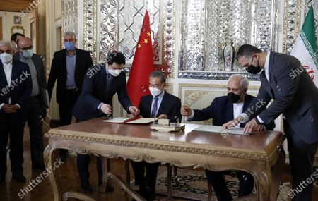 Iranian foreign minister Mohammad Javad Zarif (R) and Chinese foreign minister Wang Yi (L) sign documents during a document signing ceremony in Tehran, Iran, 27 March 2021. Zarif and Yi have signed a 25-year Iran and China strategic partnership act.