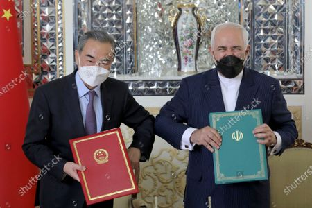 Iranian Foreign Minister Mohammad Javad Zarif, right, and his Chinese counterpart Wang Yi, pose for photos after the ceremony of signing documents, in Tehran, Iran, . Iran and China on Saturday signed a 25-year strategic cooperation agreement addressing economic issues amid crippling U.S. sanctions on Iran, state TV reported