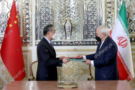 Iranian Foreign Minister Mohammad Javad Zarif, right, and his Chinese counterpart Wang Yi, exchange signed cooperation documents, in Tehran, Iran, . Iran and China on Saturday signed a 25-year strategic cooperation agreement addressing economic issues amid crippling U.S. sanctions on Iran, state TV reported
