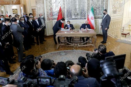 Iranian Foreign Minister Mohammad Javad Zarif, right, and his Chinese counterpart Wang Yi, sign agreements after their talks in Tehran, Iran, . Iran and China on Saturday signed a 25-year strategic cooperation agreement addressing economic issues amid crippling U.S. sanctions on Iran, state TV reported