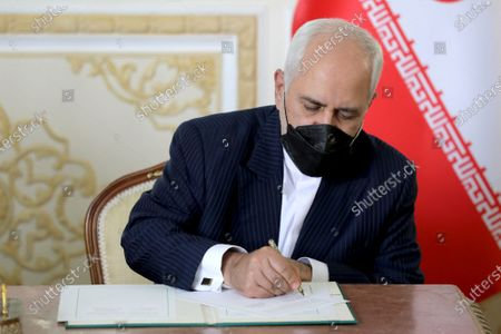 Iranian Foreign Minister Mohammad Javad Zarif signs a cooperation agreement, after his talk with his Chinese counterpart Wang Yi, in Tehran, Iran, . Iran and China on Saturday signed a 25-year strategic cooperation agreement addressing economic issues amid crippling U.S. sanctions on Iran, state TV reported