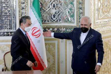 Iranian Foreign Minister Mohammad Javad Zarif, right, gestures to his Chinese counterpart Wang Yi after the ceremony of signing documents, in Tehran, Iran, . Iran and China on Saturday signed a 25-year strategic cooperation agreement addressing economic issues amid crippling U.S. sanctions on Iran, state TV reported