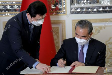 Chinese Foreign Minister Wang Yi signs a cooperation agreement, after his talk with his Iranian counterpart Mohammad Javad Zarif, in Tehran, Iran, . Iran and China on Saturday signed a 25-year strategic cooperation agreement addressing economic issues amid crippling U.S. sanctions on Iran, state TV reported