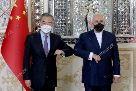Iranian Foreign Minister Mohammad Javad Zarif, right, and his Chinese counterpart Wang Yi, pose for photos at the start of their meeting in Tehran, Iran, . Iran and China on Saturday signed a 25-year strategic cooperation agreement addressing economic issues amid crippling U.S. sanctions on Iran, state TV reported