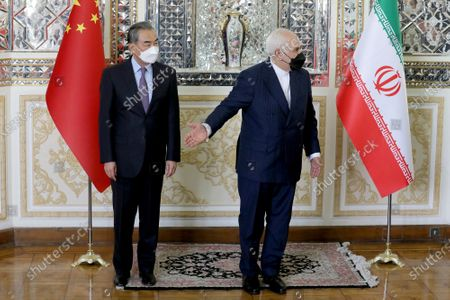 Iranian Foreign Minister Mohammad Javad Zarif, right, welcomes Chinese Foreign Minister Wang Yi at the start of their meeting, in Tehran, Iran, . Iran and China on Saturday signed a 25-year strategic cooperation agreement addressing economic issues amid crippling U.S. sanctions on Iran, state TV reported