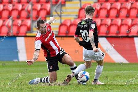 Lewis Page (20) of Exeter City is challenged by Ashley Hunter (10) of Salford City during the EFL Sky Bet League 2 match between Exeter City and Salford City at St James' Park, Exeter
