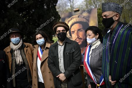 Ahmad Massoud (C), son of late Afghan commander Ahmad Shah Massoud, former Afghan President Hamid Karzai (R) and Paris Mayor Anne Hidalgo (2-L) pose in front of a portrait by photographer Reza (L) of the late commander Massoud during a ceremony to unveil a commemorative plaque in his honour in an alley along the Champs-Elysees Avenue in Paris, France, 27 March 2021.