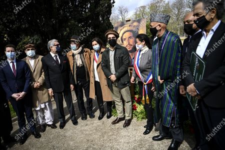 Ahmad Massoud (C), son of late Afghan commander Ahmad Shah Massoud, former Afghan president Hamid Karzai (3-R) and Paris mayor Anne Hidalgo (C-L) pose in front of a portrait by photographer Reza (4thL) of the late commander Massoud during a ceremony to unveil a commemorative plaque in his honour in an alley along the Champs-Elysees avenue in Paris, France, 27 March 2021.