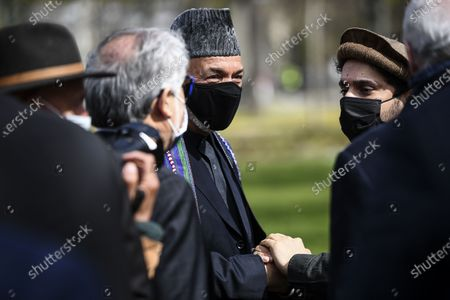 Ahmad Massoud (R), son of late Afghan commander Ahmad Shah Massoud, holds hands with former Afghan President Hamid Karzai during a ceremony to unveil a commemorative plaque in honour of late Afghan anti-Taliban commander Massoud in an alley along the Champs-Elysees Avenue in Paris, France, 27 March 2021.