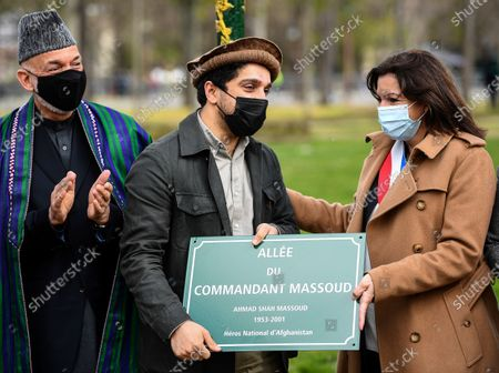 Ahmad Massoud, son of late Afghan commander Ahmad Shah Massoud, center, holds a spare plaque flanked by former Afghan President Hamid Karzai, left, and Paris Mayor Anne Hidalgo after they unveiled a commemorative plaque in honor of late Afghan anti-Taliban commander Massoud in an alley along the Champs Elysees Avenue in Paris