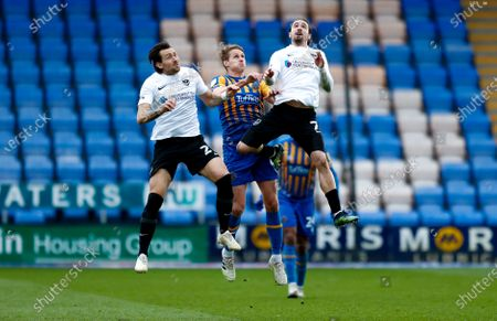 Portsmouth defender Charlie Daniels (21)   , Shrewsbury Town midfielder David Edwards (4)  and Portsmouth midfielder Ryan Williams (7) challenge in the air during the EFL Sky Bet League 1 match between Shrewsbury Town and Portsmouth at Montgomery Waters Meadow, Shrewsbury