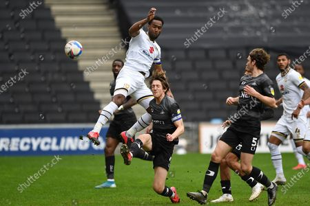 MK Dons' Forward Cameron Jerome (35) and Doncaster defender Tom Anderson (4) battles for possession during the EFL Sky Bet League 1 match between Milton Keynes Dons and Doncaster Rovers at stadium:mk, Milton Keynes