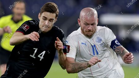 Germany's Florian Neuhaus, left, and Iceland's Holmbert Aron Friojonsson, right challenge for the ball during the World Cup 2022 group J qualifying soccer match between Germany and Iceland in Duisburg, Germany, . In the background is Germany's Joshua Kimmich