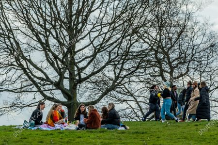 Stock Photo of People are already breaking the 'rule of 6' with two days left of only meeting one other person outside rule - here gathering near the 'stone of free speech' a meeting point. Fine weather in Hampstead encourages people to meet outdoors a few days before the next stage of the easing of lockdown 3.