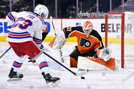 Philadelphia Flyers goaltender Brian Elliott looks to make a save on a shot from New York Rangers' Adam Fox (23) during the second period of an NHL hockey game, in Philadelphia