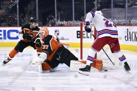 Philadelphia Flyers goaltender Brian Elliott makes a pad save on a shot from New York Rangers' Adam Fox, right, during the second period of an NHL hockey game, in Philadelphia