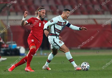 Serbia's Nemanja Gudelj, left, and Portugal's Cristiano Ronaldo challenge for the ball during the World Cup 2022 group A qualifying soccer match between Serbia and Portugal at the Rajko Mitic stadium in Belgrade, Serbia