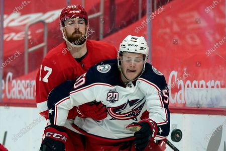 Detroit Red Wings defenseman Filip Hronek (17) holds Columbus Blue Jackets left wing Eric Robinson (50) during the third period of an NHL hockey game, in Detroit