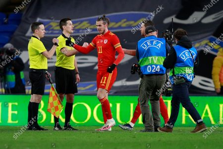 Wales' Gareth Bale (11) bumps fists with referees after beating 1-0 Mexico during a friendly soccer match at the Cardiff City Stadium, in Cardiff, Wales