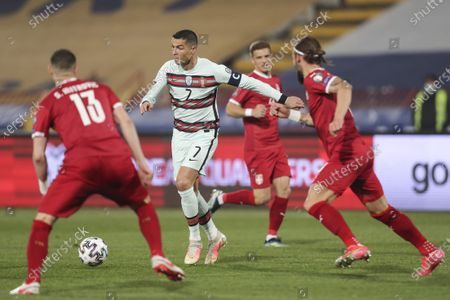 Serbia's Stefan Mitrovic (L) and Nemanja Gudelj (R) fight for the ball with Portugal's Cristiano Ronaldo (C) during the Group A of FIFA World Cup Qatar 2022 qualifier match at Rajko Mitic Stadium in Belgrade, Serbia, 27 March 2021.