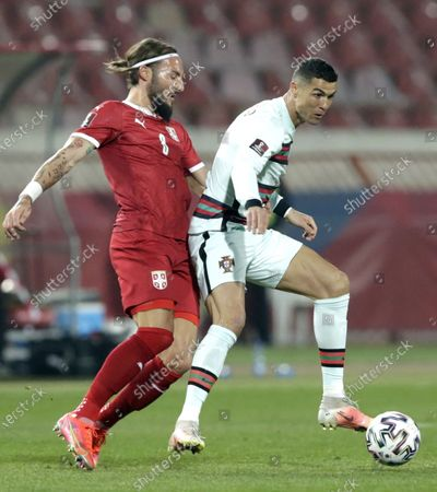 Portugal's Cristiano Ronaldo (R) in action against Serbia's Nemanja Gudelj (L) during the FIFA World Cup 2022 qualifying soccer match between Serbia and Portugal in Belgrade, Serbia, 27 March 2021.