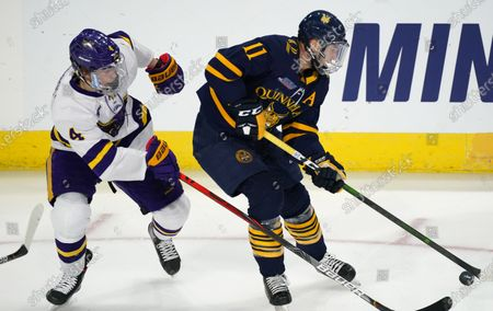 Stock Image of Quinnipiac forward Wyatt Bongiovanni, right, looks to pass the puck as Minnesota St. defenseman Andy Carroll covers in the first period of an NCAA West Regional college hockey semifinal game, in Loveland, Colo