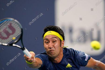 Yasutaka Uchiyama, of Japan, reaches for a shot from Diego Schwartzman, of Argentina, during the Miami Open tennis tournament, in Miami Gardens, Fla