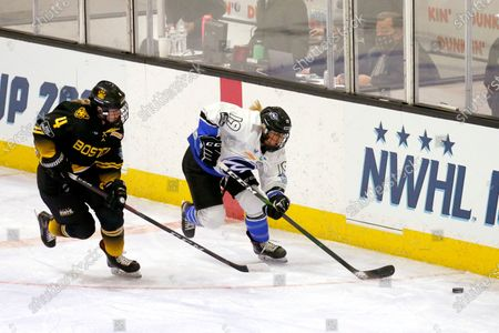 Boston Pride defender Lauren Kelly(4) and Minnesota Whitecaps forward Haley Mack (19) compete for the puck along the boards during the first period of the NWHL Isobel Cup championship game, in Boston