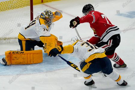 Stock Photo of Nashville Predators goaltender Juuse Saros, left, makes a save on a shot by Chicago Blackhawks center Kirby Dach, right, as Predators defenseman Jeremy Davies watches during the first period of an NHL hockey game in Chicago