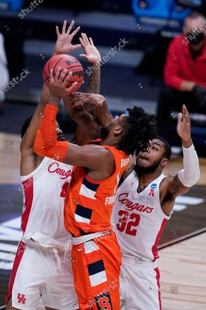 Syracuse forward Quincy Guerrier (1) drives on Houston forward Justin Gorham (4) and Reggie Chaney (32) in the first half of a Sweet 16 game in the NCAA men's college basketball tournament at Hinkle Fieldhouse in Indianapolis
