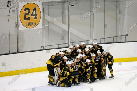 Boston Pride players pose for a photo under a banner honoring Denna Laing after winning the NWHL Isobel Cup championship hockey game, in Boston