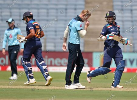 England's Ben Stokes, second right, reacts as India's Shikhar Dhawan, right, and Rohit Sharma, second left, run between the wickets during the third One Day International cricket match between India and England at Maharashtra Cricket Association Stadium in Pune, India