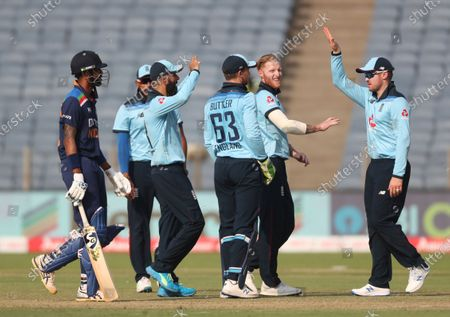 England's Ben Stokes, second right, celebrates with teammates the dismissal of India's Hardik Pandya during the third One Day International cricket match between India and England at Maharashtra Cricket Association Stadium in Pune, India