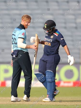 England's Ben Stokes, left, checks out the bat of India's Shardul Thakur after he was hit for a six during the third One Day International cricket match between India and England at Maharashtra Cricket Association Stadium in Pune, India