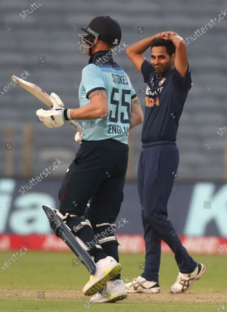 India's Bhuvneshwar Kumar, right, reacts after bowling a delivery to England's Ben Stokes, left, during the third One Day International cricket match between India and England at Maharashtra Cricket Association Stadium in Pune, India