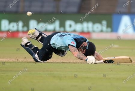 England's Ben Stokes dives to make it to the crease during the third One Day International cricket match between India and England at Maharashtra Cricket Association Stadium in Pune, India