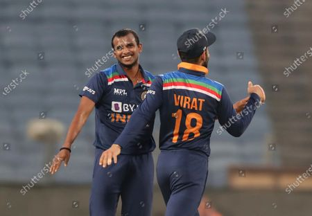 Stock Image of India's T Natrajan, left, celebrates with captain Virat Kohli after the dismissal of England's Ben Stokes during the third One Day International cricket match between India and England at Maharashtra Cricket Association Stadium in Pune, India